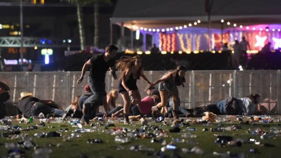 Des gens s'enfuient du parterre d'un festival où d'autres personnes demeurent allongées.