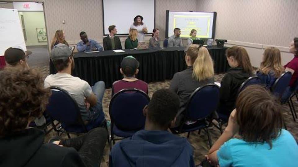 Dans une salle, des jeunes sont assis sur des sièges devant une longue table ont sont également assis huit personnes.