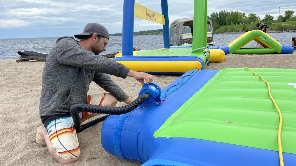Le directeur général du parc Octopus, Evens Pelletier gonfle un module du jeu aquatique.