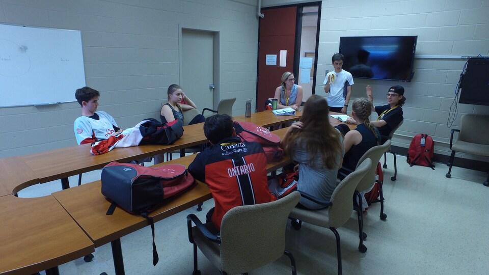 L'équipe Ontario en réunion avec leur entraîneur qui lance de l'argent dans les airs.