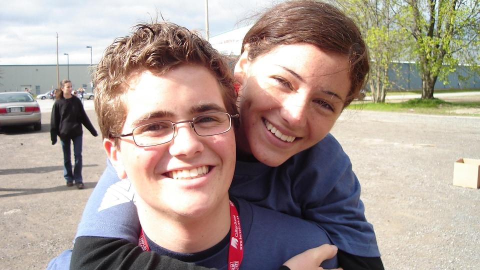 Le jeune homme est à gauche et il porte des verres. La jeune femme à droite l'enlace par derrière. Les deux affichent un large sourire.