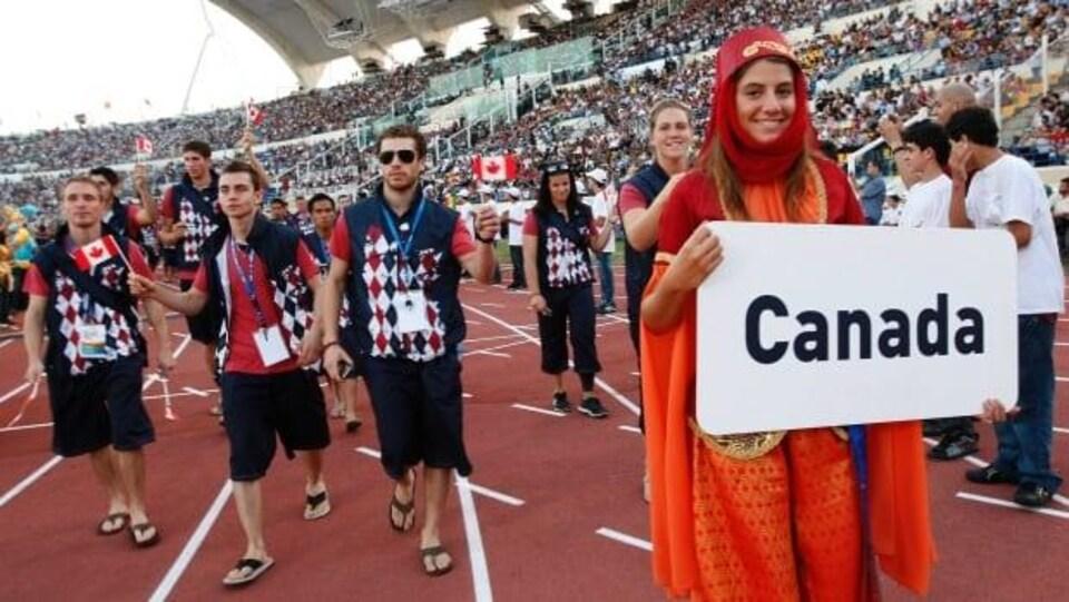 La délégation du Canada marche sur la piste d'un stade. Une foule occupe tous les gradins.
