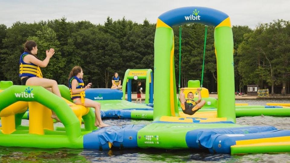 Des enfants s'amusent sur des jeux gonflables flottants.