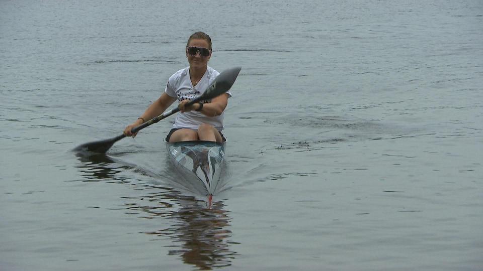 Elle est dans son kayak sur l'eau.
