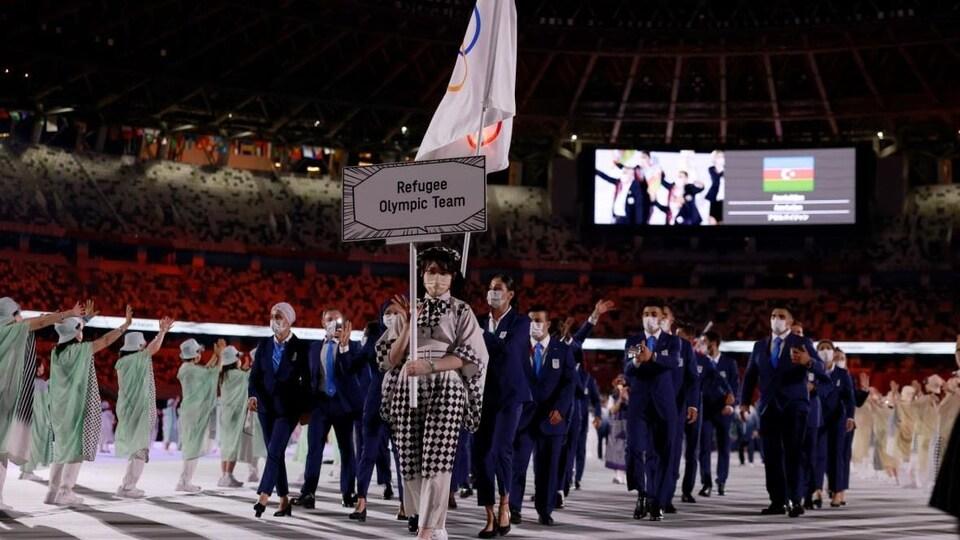 Les athlètes de l'équipe olympique des réfugiés défilent lors de la cérémonie d'ouverture des Jeux de Tokyo.