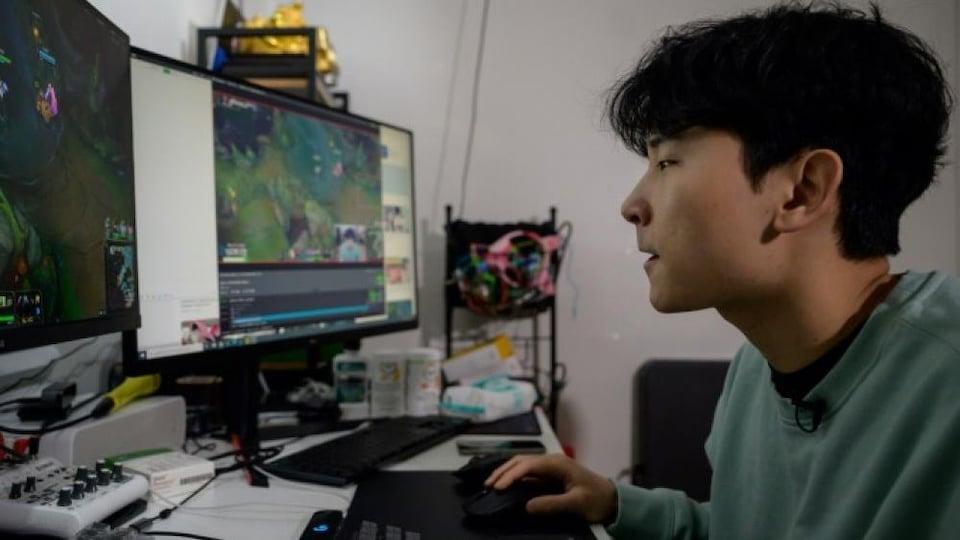 Un homme en train de jouer à un jeu vidéo devant deux écrans d'ordinateur.