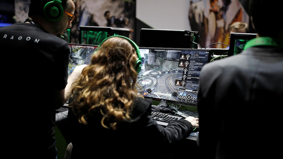 Un visiteur aux cheveux blonds assis de dos joue à un jeux vidéo.