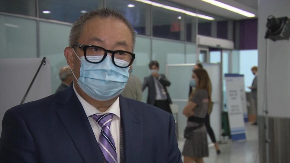 Un homme avec des lunettes et un masque répond aux questions des journalistes.