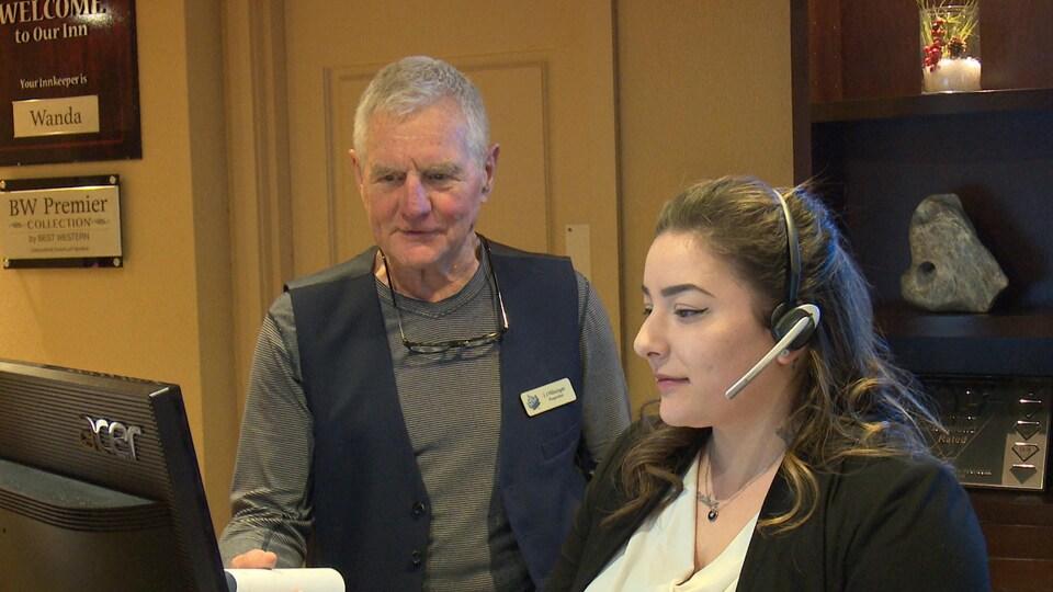 Jim Hilsinger parle à une employée se tenant debout derrière une réception d'hôtel.