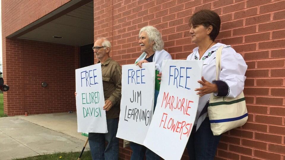 Trois protestants réclamant d'être libérés pendant une manifestation contre Muskrat Falls