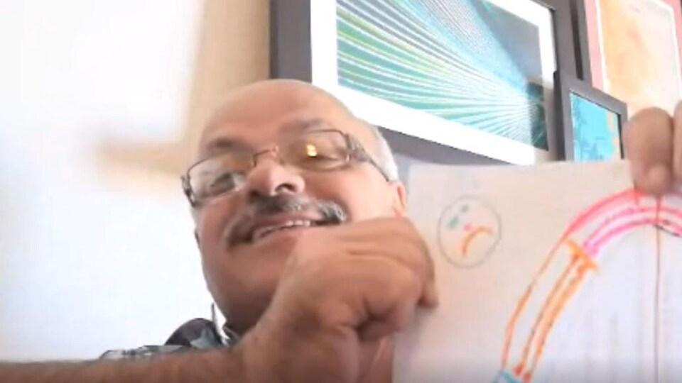 Jim Lebreton avec une image d'un arc-en-ciel et un dessin d'un homme triste.