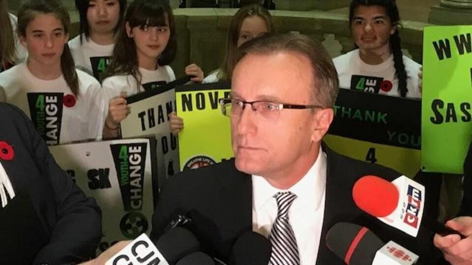 Jim Reiter en point de presse où l'on voit plusieurs enfants derrière lui tenant des pancartes.