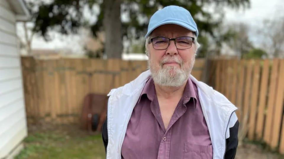Un homme avec un chapeau et des lunettes devant une clôture.