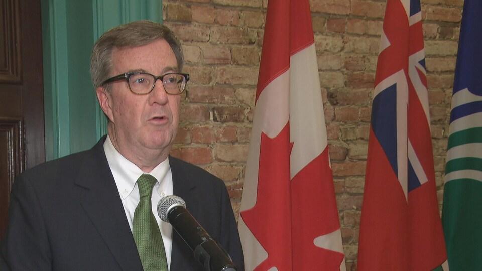 Un homme qui porte des lunettes devant un micro.