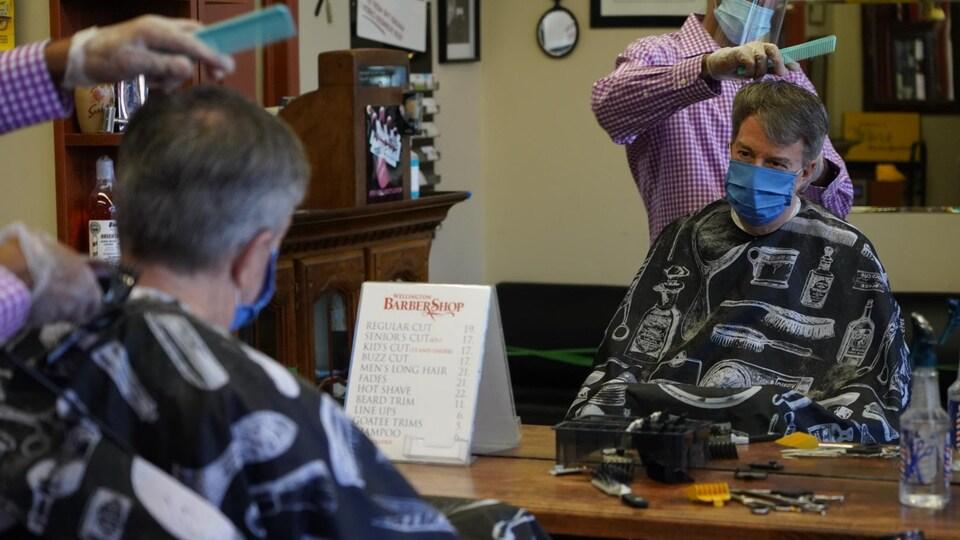 Un homme portant un masque se fait couper les cheveux par un autre homme muni de gants, d'une visière et d'un masque.