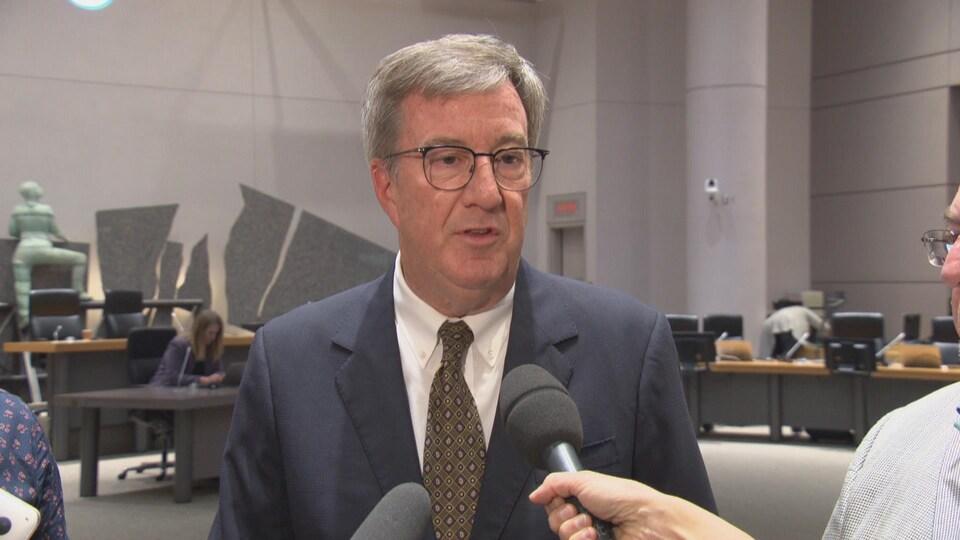 Jim Watson s'adresse aux médias dans la salle du conseil municipal.