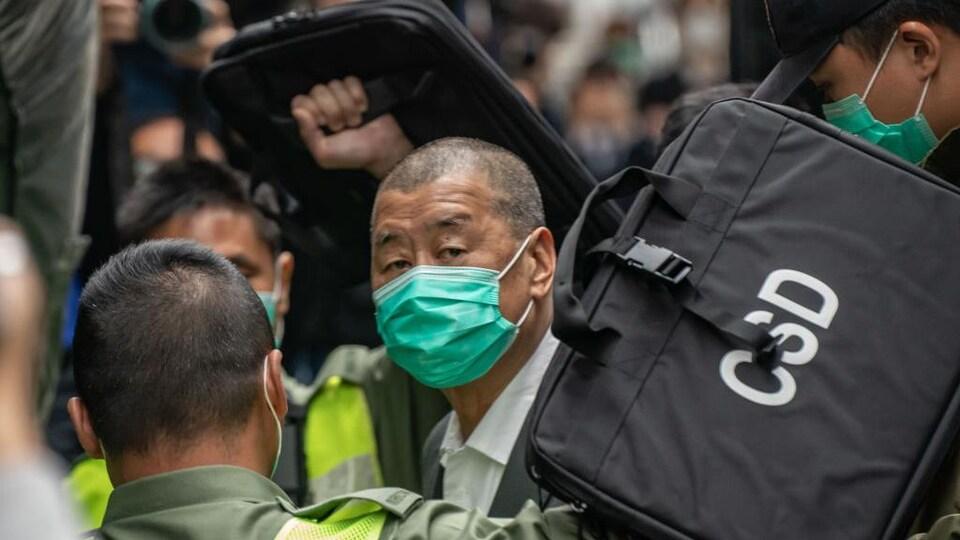 Dans la foule, un homme au crâne rasé et portant un masque regarde au loin.