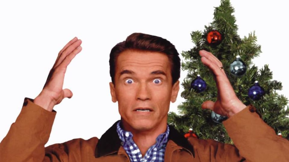Un père devant un sapin de Noël se prend la tête, l'air stressé.