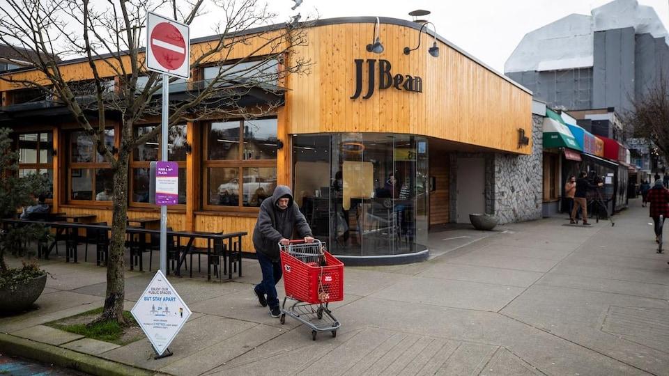 Un homme pousse un chariot d'épicerie devant un café JJ Bean à Vancouver.