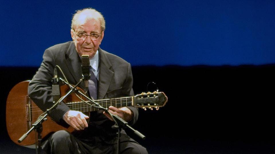 Le chanteur est assis face au micro, une guitare à la main, sur scène.