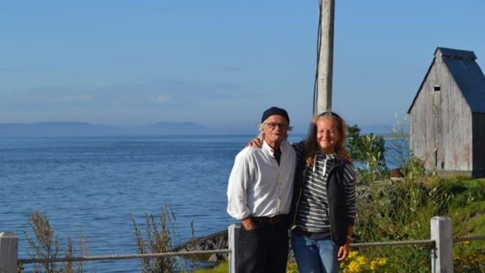Un homme et une femme debout devant un cours d'eau.
