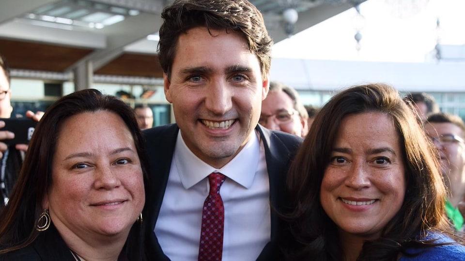 Deux femmes souriantes dans la quarantaine dont la députée Jody Wilson-Raybould posent en compagnie du premier ministre Justin Trudeau.