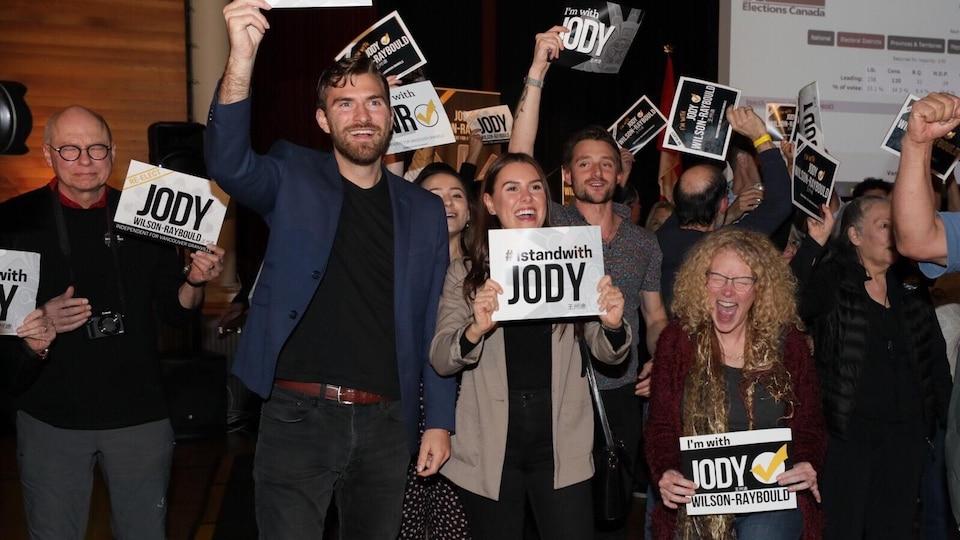 Des gens qui tiennent des affiches avec le nom de Jody Wilson-Raybould crient victoire.