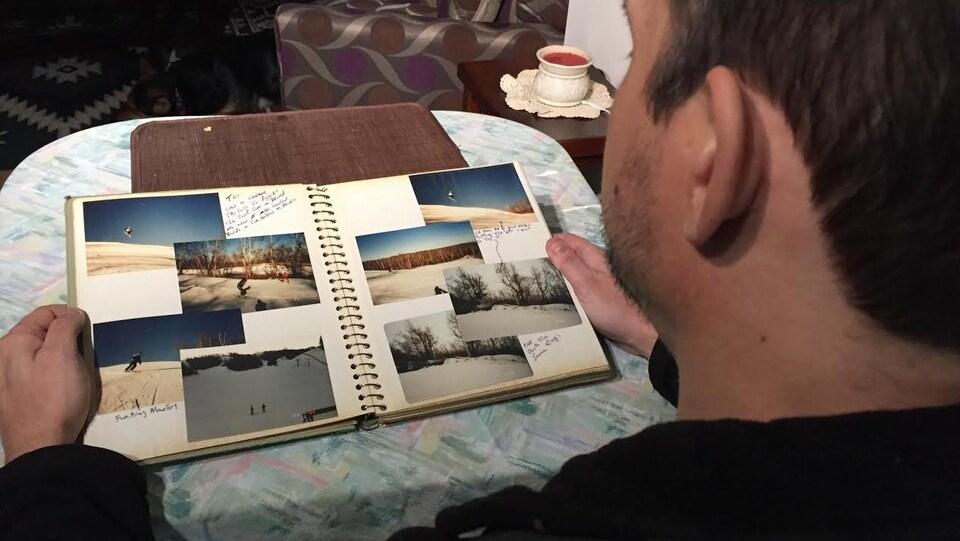 Un homme, vu de dos, qui regarde un album de photos.