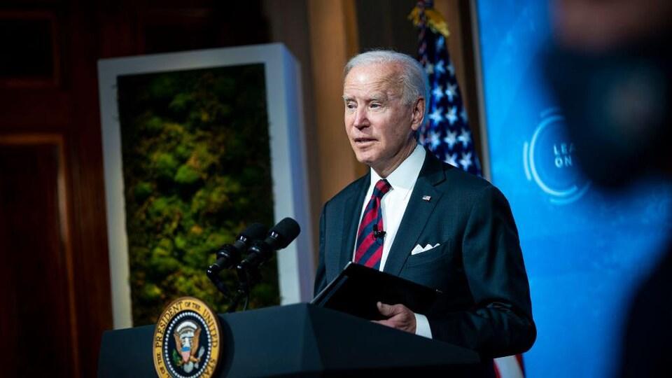 Le président Biden parle derrière une tribune.