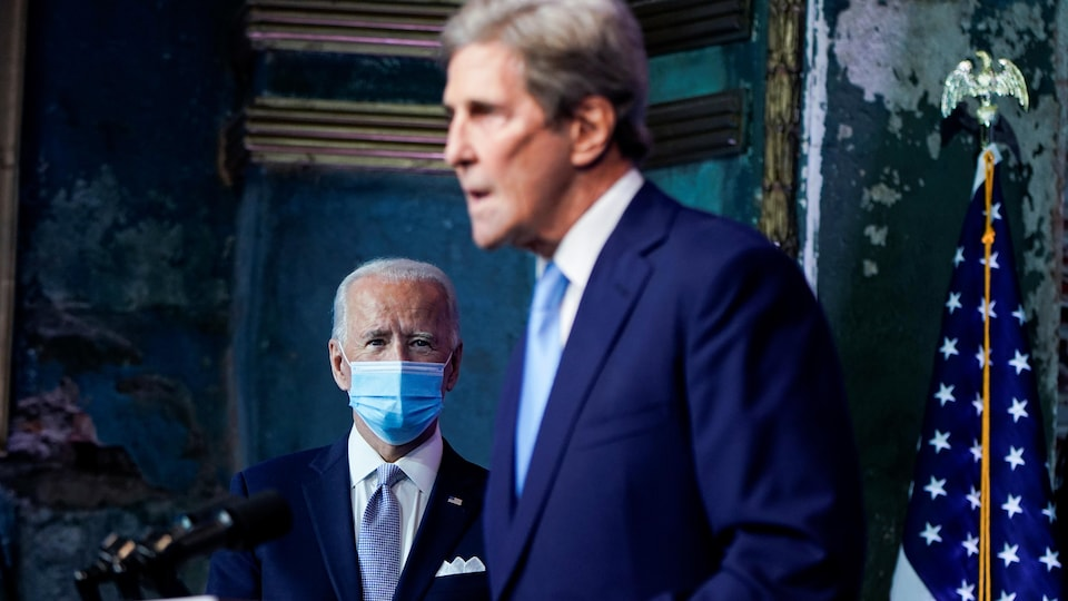 Joe Biden observe John Kerry qui parle debout devant un lutrin.