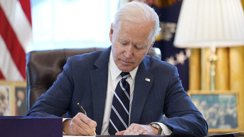 Le président Joe Biden, assis à son bureau, à la Maison-Blanche, signe un document.