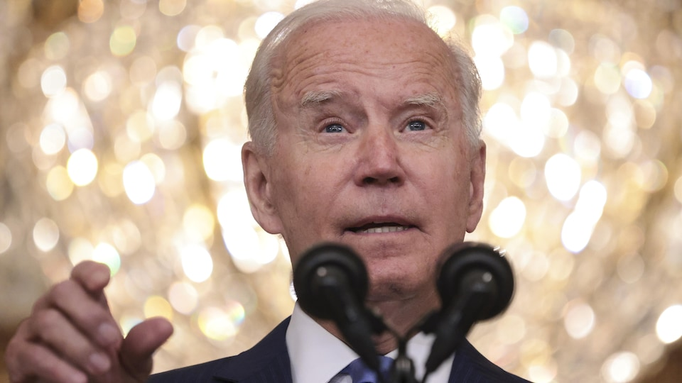 Joe Biden parle dans un micro, devant une boule lumineuse.