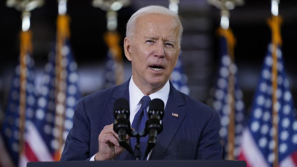 Joe Biden parle au micro devant des drapeaux américains.
