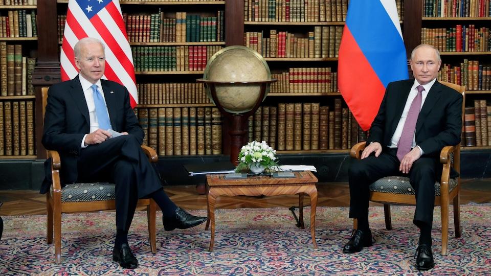 Les deux hommes sont assis sur des chaises à bonne distance dans une bibliothèque.