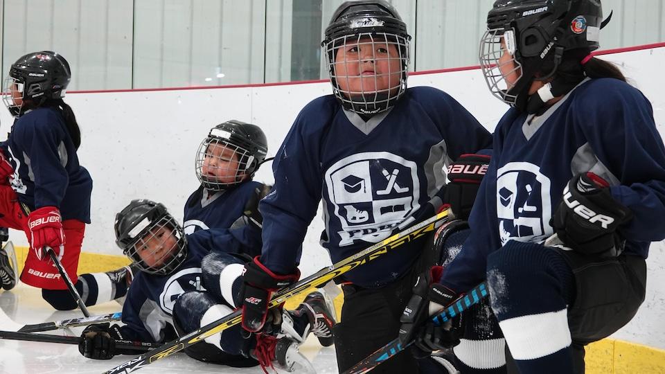 Les jeunes joueurs de hockey se préparent pour un exercice de patin.