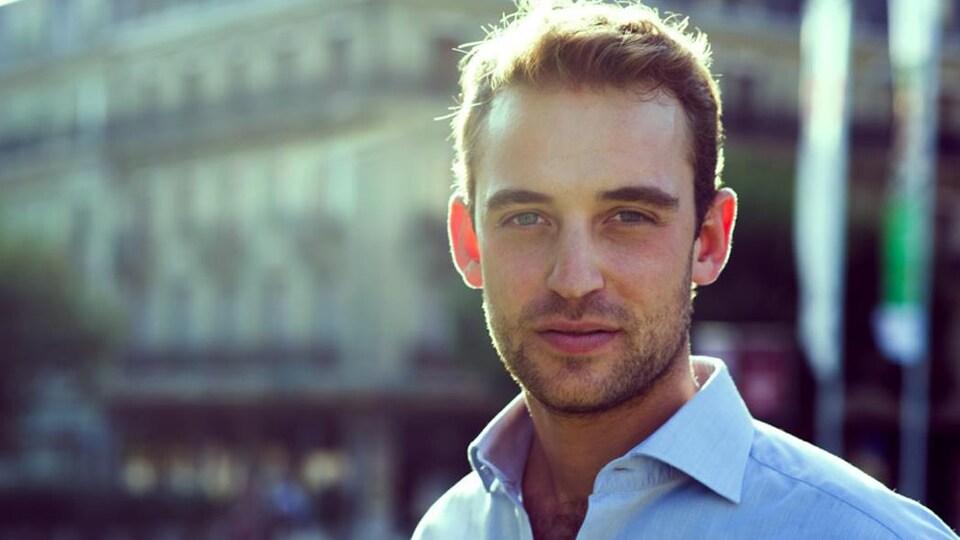 Gros plan sur un homme aux yeux bleus, cheveux et barbe courts, sur fond de décor urbain.