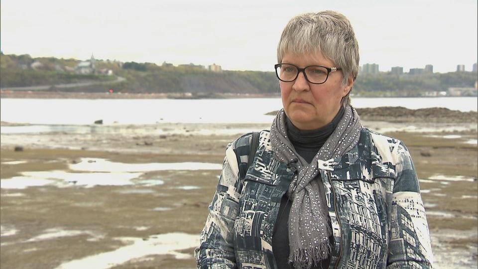 Une femme portant des lunettes sur le bord d'un cours d'eau.