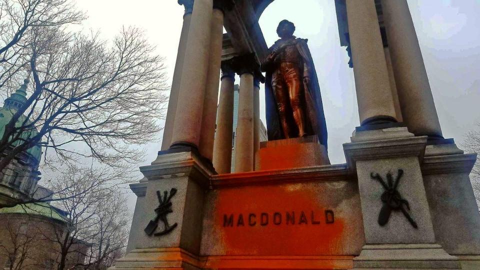 Le nom de MacDonald est maculé de peinture orange, tout comme la statue.