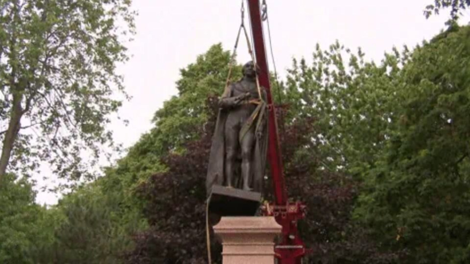 Une grue soulève la statue.