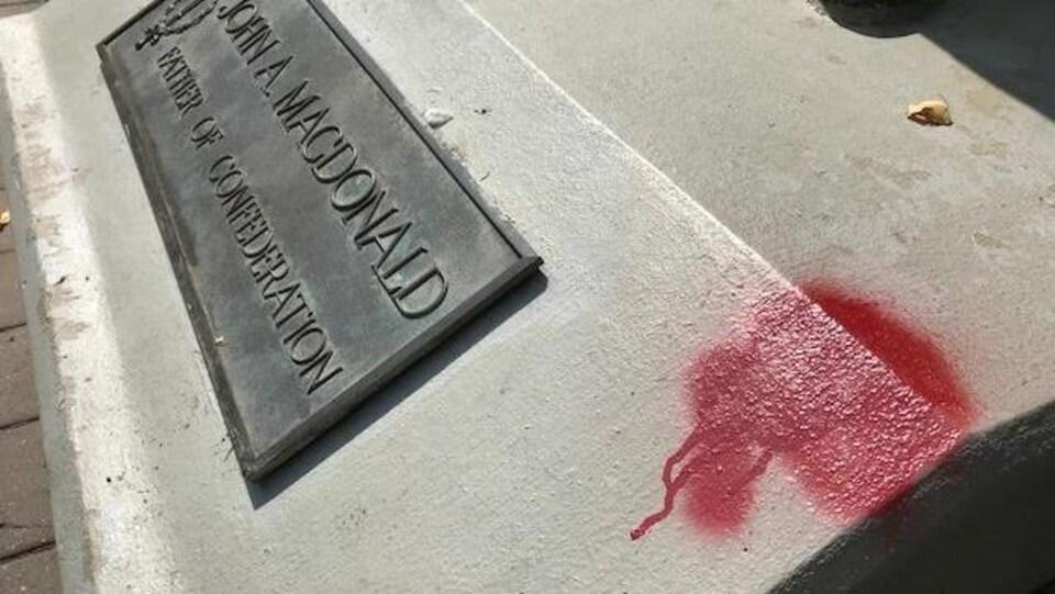 Tache de peinture rouge sur le socle, à côté de la plaque indiquant son nom et son titre de Père de la Confédéraiton.