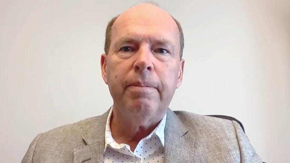 Un homme en chemise blanche à pois et en veston gris devant sa webcam.