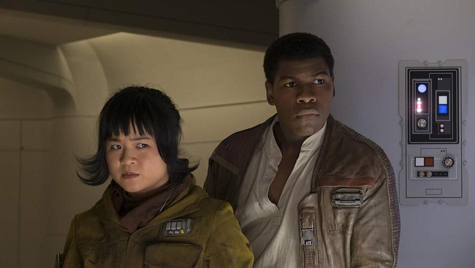 Kelly Marie Tran et John Boyega regardent avec méfiance quelque chose alors qu'ils se trouvent dans un vaisseau.