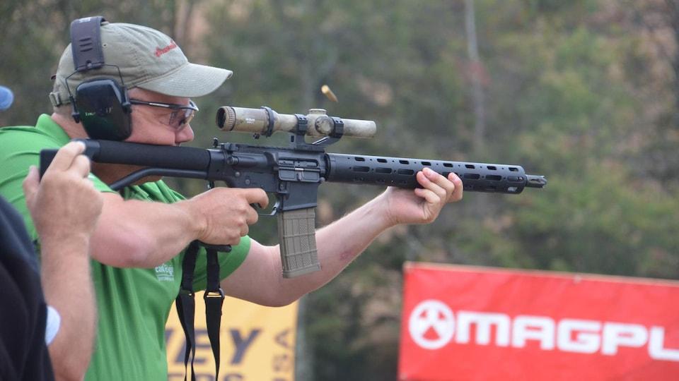 Un homme a une arme dans les mains pendant une compétition.