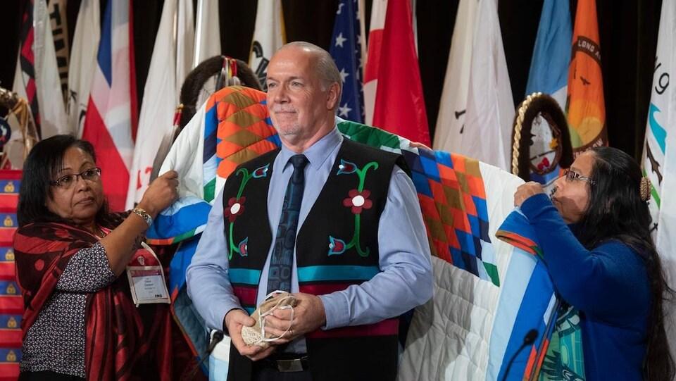 Le Premier ministre John Horgan reçoit une couverture lors d'une cérémonie à l'Assemblée extraordinaire des chefs des Premières Nations.