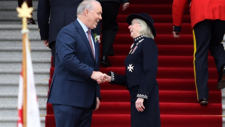 Le premier ministre John Horgan et la lieutenante-gouverneure, Judith Guichon, se serrent la main devant le Parlement à Victoria