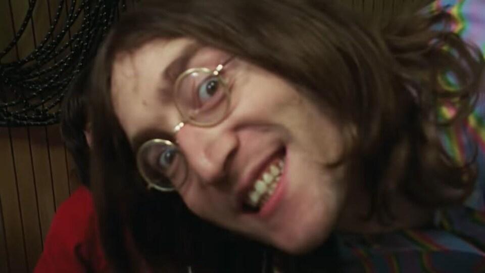 John Lennon grimace d'un air inquiétant. George Harrison peut être aperçu partiellement derrière lui.