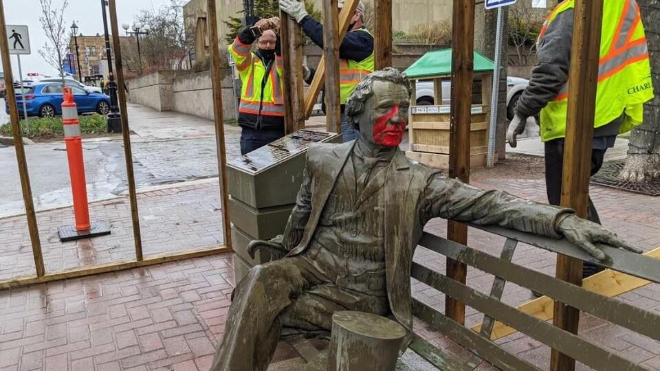 Les employés municipaux nettoient la statue dehors alors qu'il semble pleuvoir en arrière.