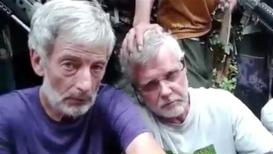 Robert Hall et John Ridsdel, assis côte à côte, sous la surveillance d'hommes armés.