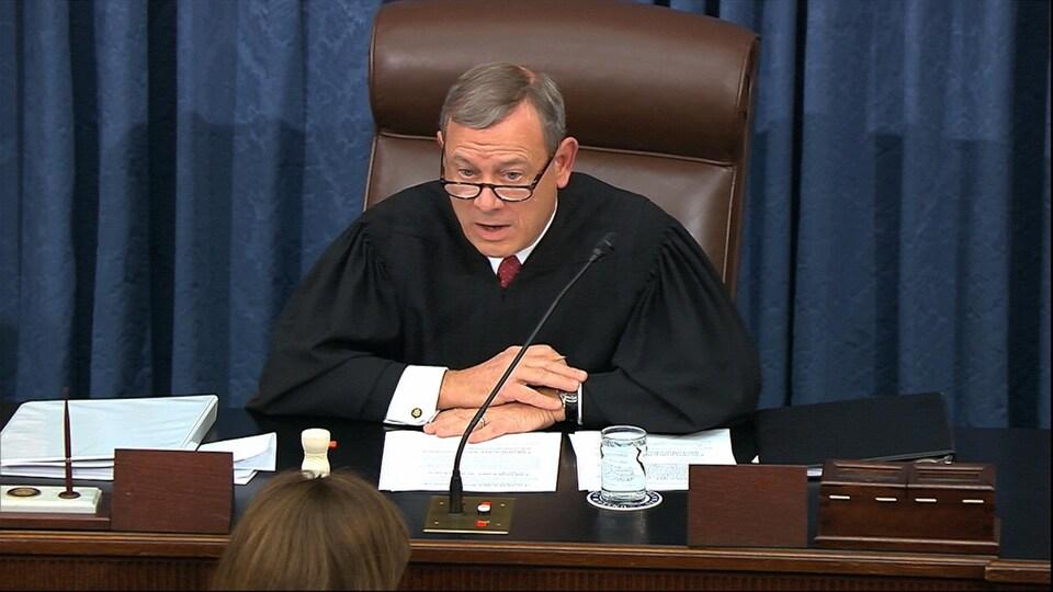 John Roberts, portant des lunettes, les bras croisés sur son bureau, s'adresse aux sénateurs