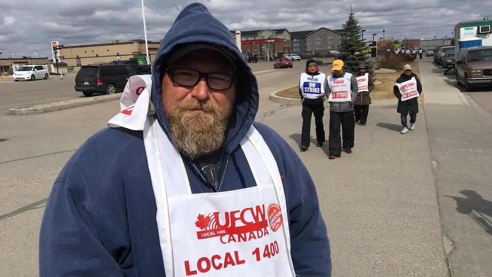 Un homme avec un capuchon bleu marine, des lunettes et une barbe avec d'autres manifestants.